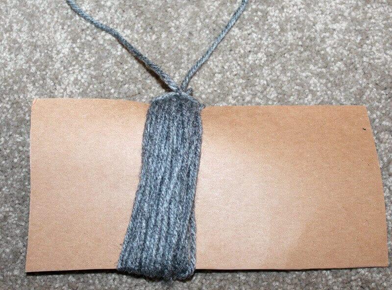 Wrap yarn around cardboard to make pompom for bookmark.