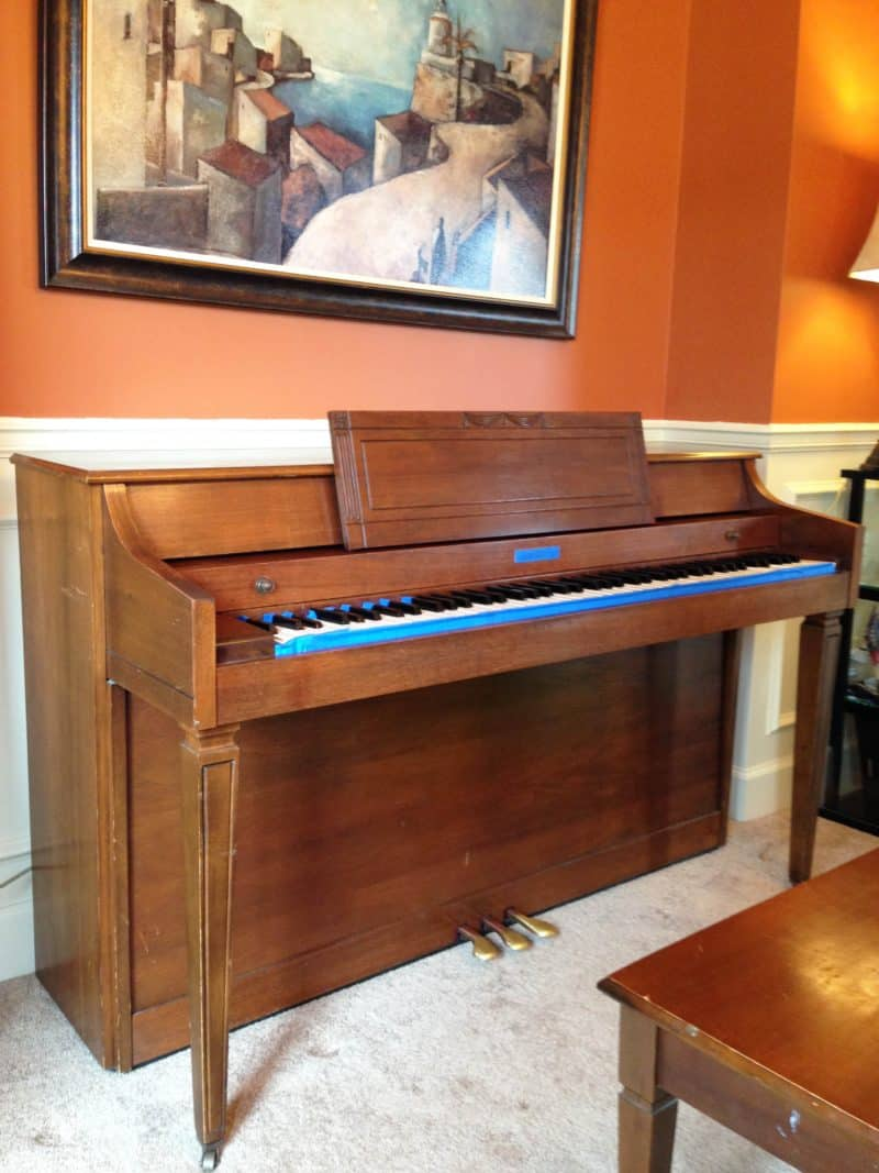 Orange wood piano prior to painting with black chalk paint