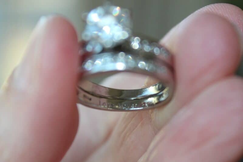 Engraving of Love Never Fails in wedding ring.