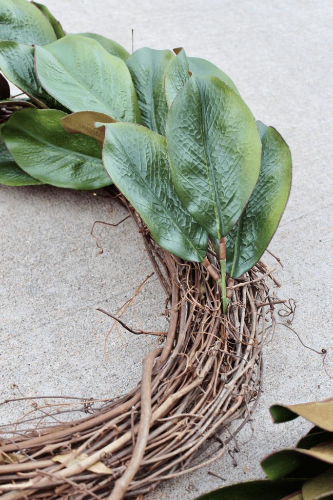 Continue adding more faux magnolia leaves to wreath