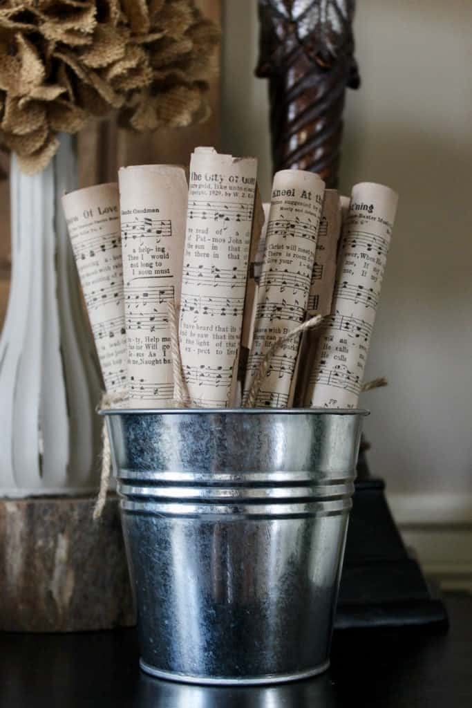 Rolled vintage music sheets tied with jute string displayed on piano.