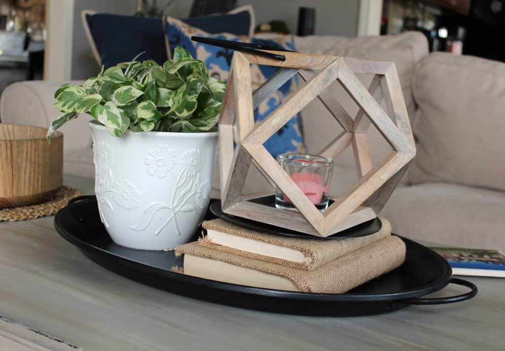 coffee table vignette using a tray, burlap covered books, plant and candle.