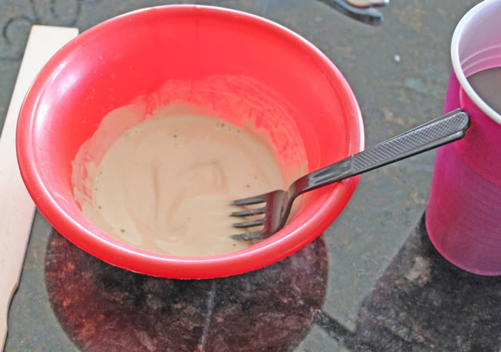 Chalk paint recipe using calcium carbonate, mixing in red plastic bowl with fork