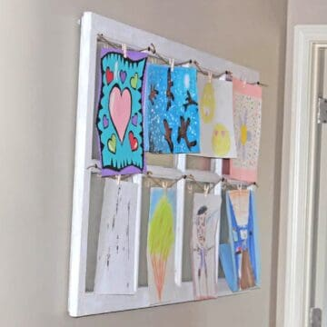 large old window on wall with twine and clothespins displaying art.
