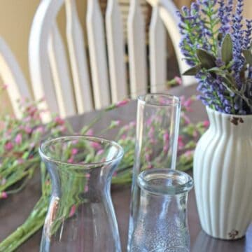 Pink and purple faux flower stems on table with vases