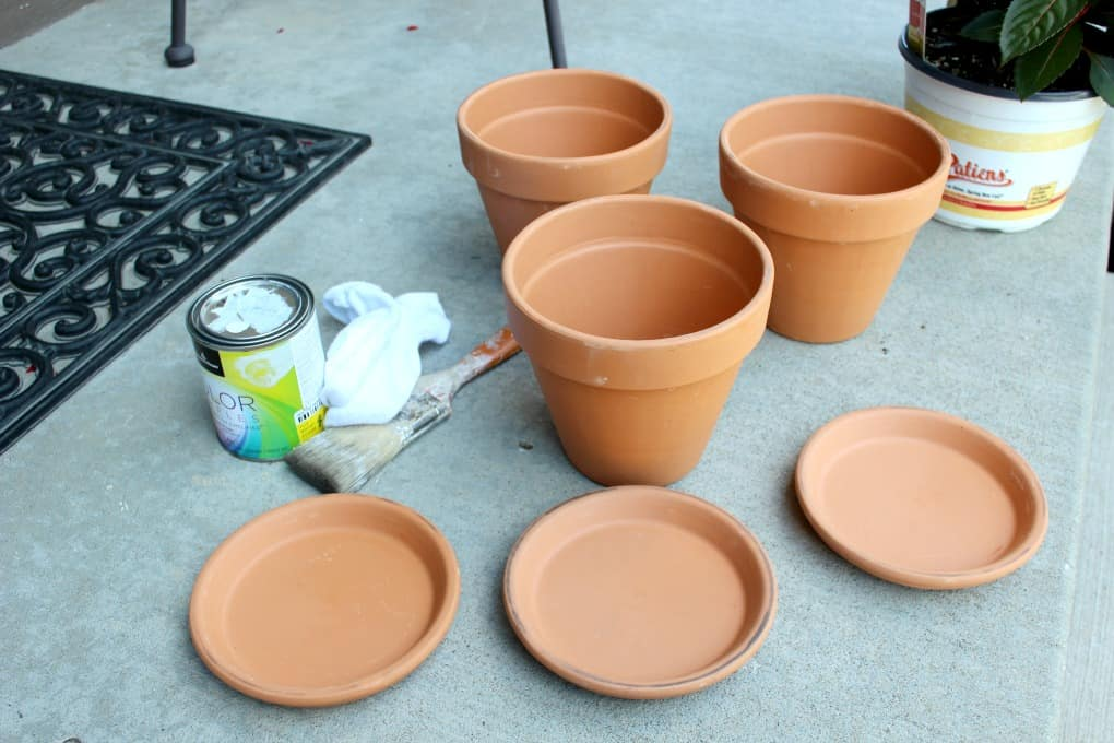 Terra cotta pots, white paint, a chip brush and old sock. Preparing to white wash pots for distressed look.