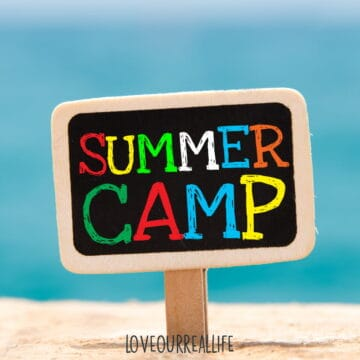 """Black sign that reads """"Summer Camp"""" in colorful lettering with sign stuck in sand."""