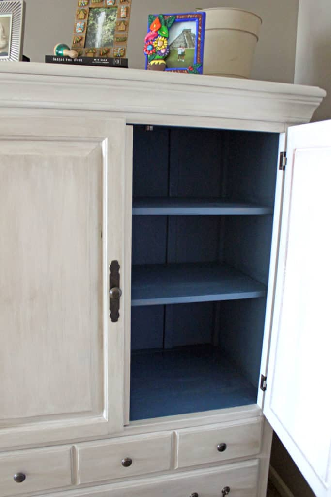 Blue painted shelving in white armoire