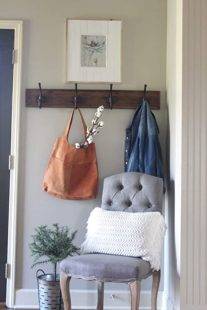 farmhouse entry with cotton stems coming out of a leather purse hung on a wooden coat rack.