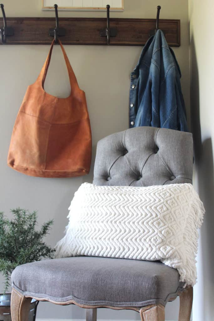 Close up view of entry way chair with ivory pillow. Jean jacket hanging on coat rack behind.
