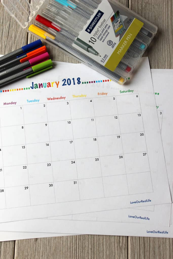 Printable monthly calendars and Staedtler pens on white washed wood background.
