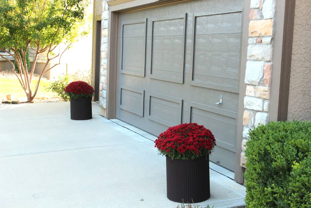 Red mums for a pop of color by brown garage doors.