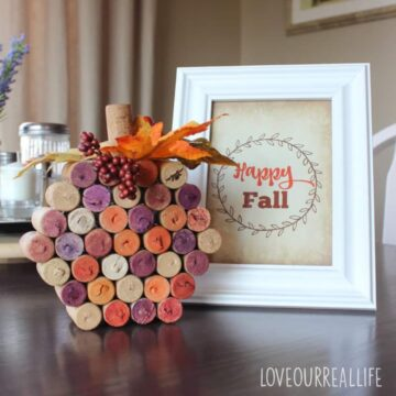 """Pumpkin made from wine corks beside sign that says """"Happy Fall""""."""