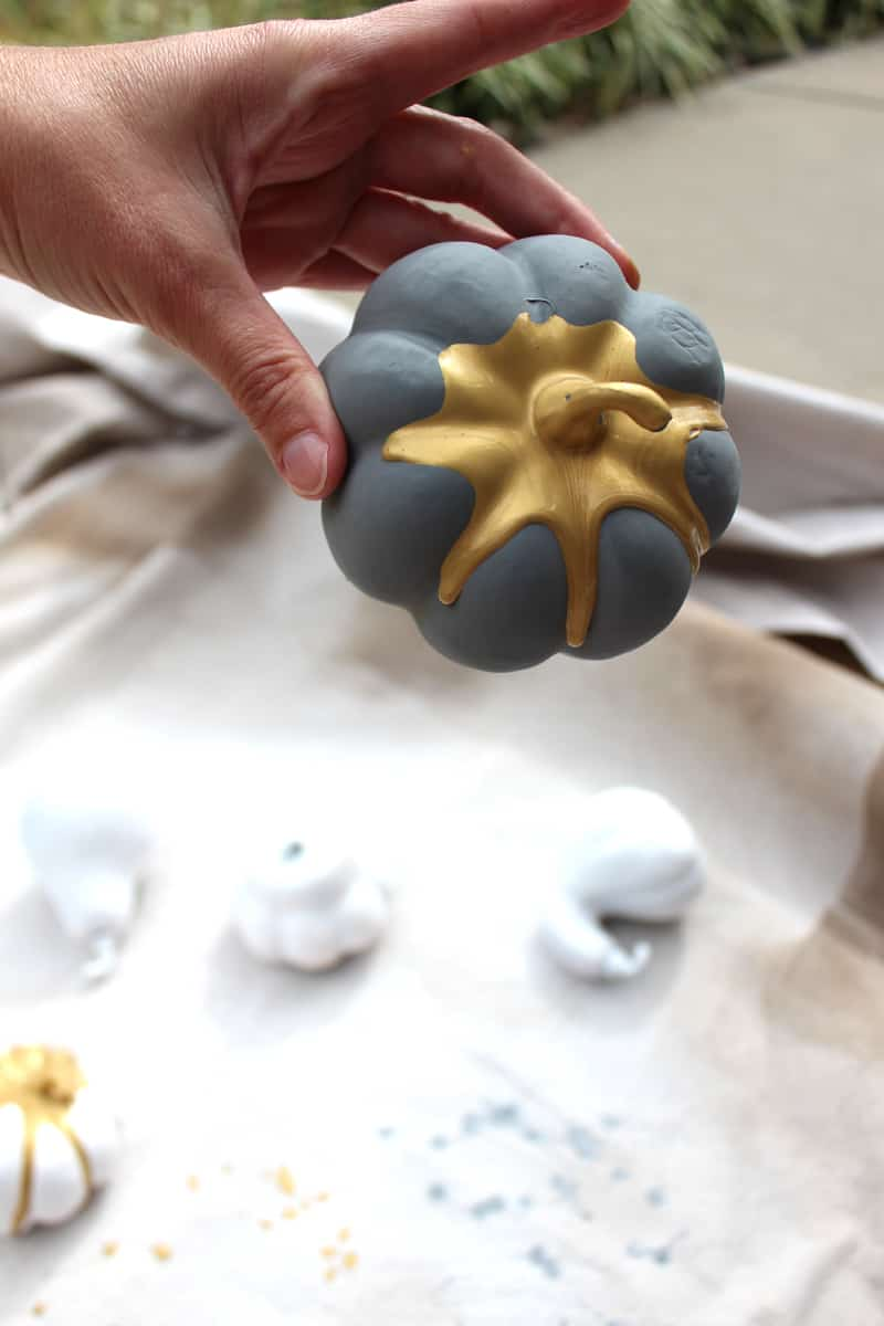 Pumpkin painting ideas: Gold metallic paint on pumpkins for DIY fall decor.