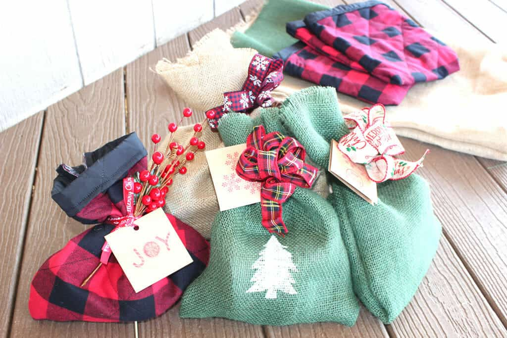 Christmas gift bags in buffalo plaid, green and tan burlap using wire ribbon bows.