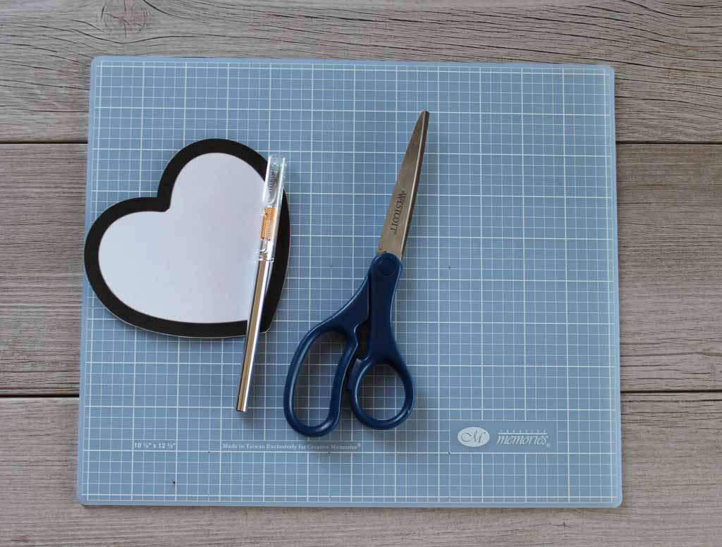 Supplies for string heart banner craft project including exacto knife, scissors, heart clip art