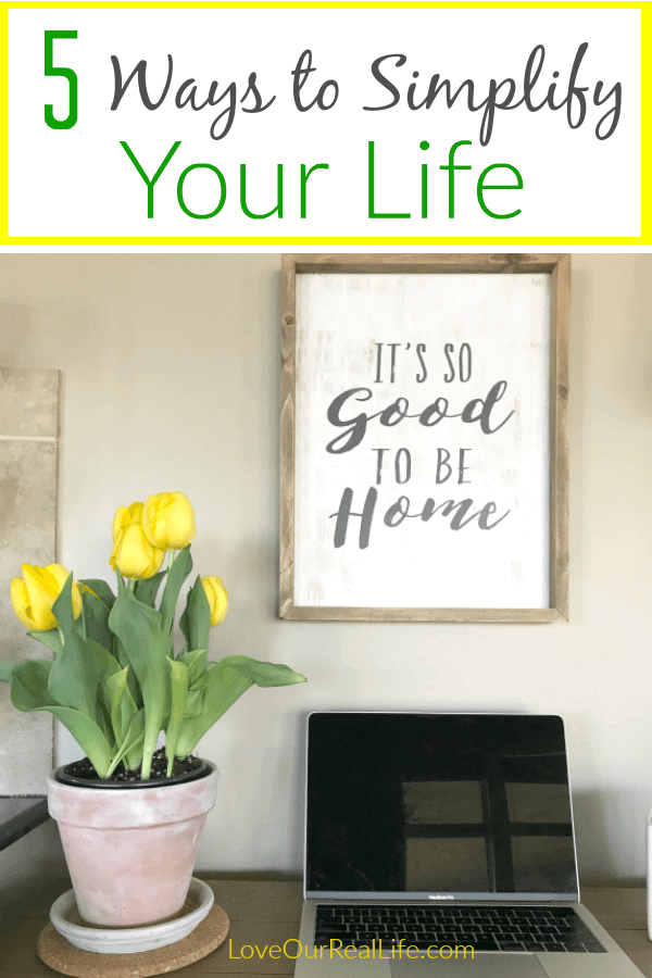"""5 Ways to Simplify your life"" on overlay with desk space, yellow tulips, computer, and wooden sign."
