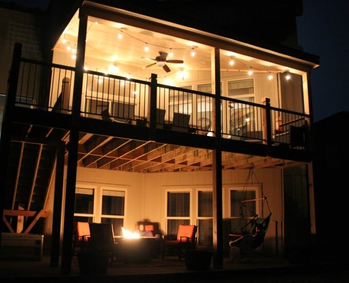 Deck and outdoor space at night with outdoor string lights and fire pit.