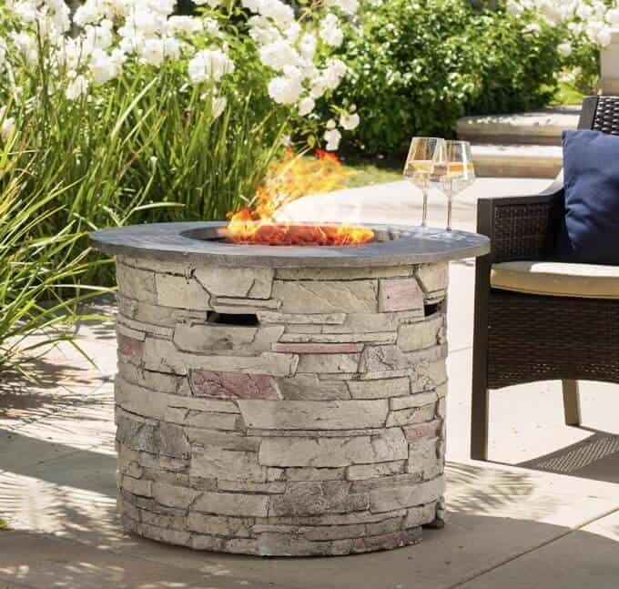Outdoor fire pit with 2 wine glasses on outer edge of table top.