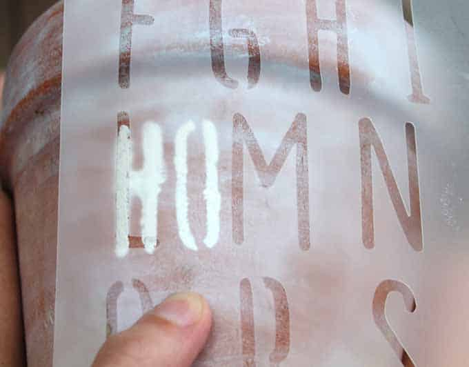 Line up the stencil for words in a straight line; how to stencil on a terra cotta pot