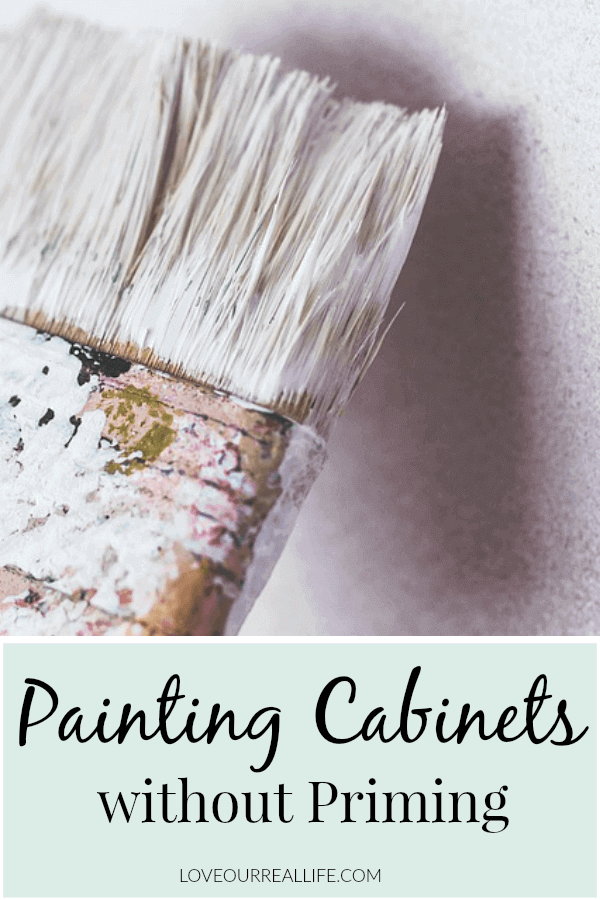 "Paint brush covered in white paint with words ""painting cabinets without priming"" on overlay"