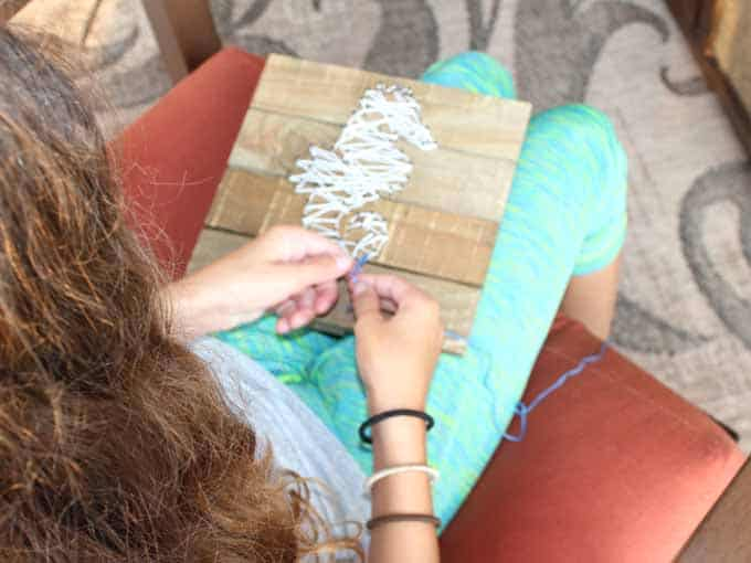 Wrap the string around the nails for string art.