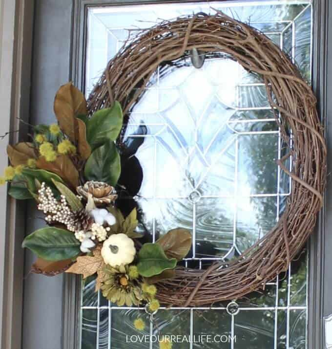 DIY Fall wreath with grape vine and fall flower stems including magnolia leaves.