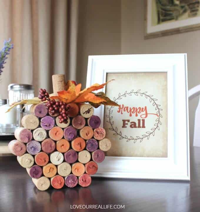 "Wine Cork Pumpkin and sign that reads ""Happy Fall"" sitting on kitchen table."