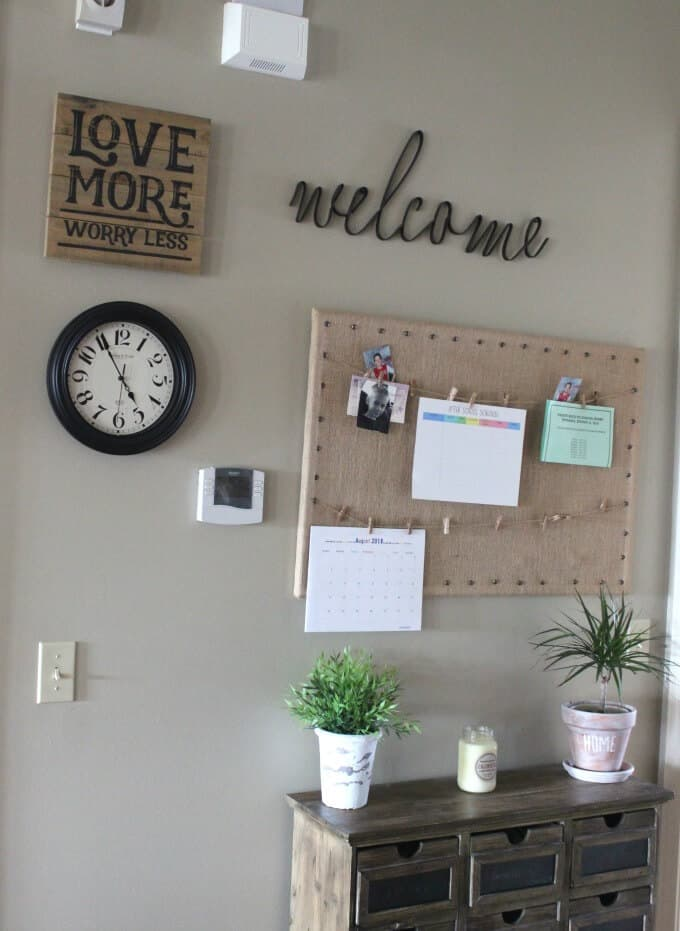 Command center with burlap bulletin board, black and white clock, welcome sign, table, and plants.