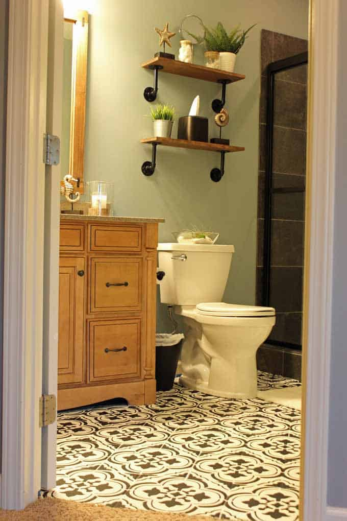 Using Santa Ana Tile Stencil by Cutting Edge Stencils used on basement bathroom tile with DIY wood shelves above toilet.
