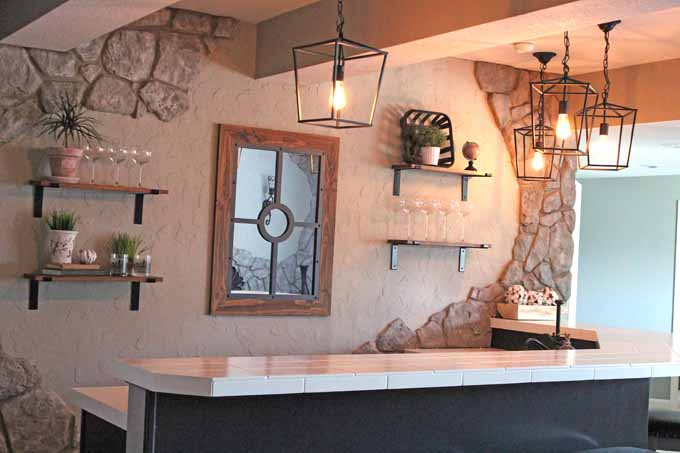 Rustic heavy duty shelves hung with dry wall anchors behind a basement bar.