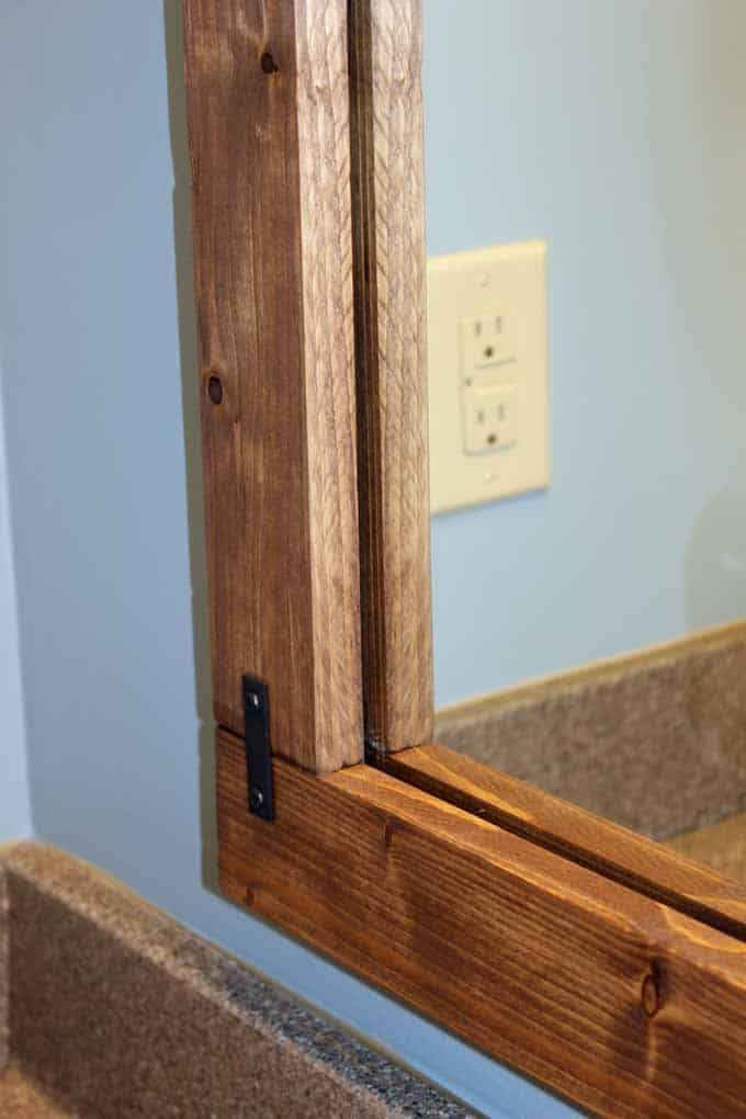 The frame lays directly over the simple bathroom mirror.