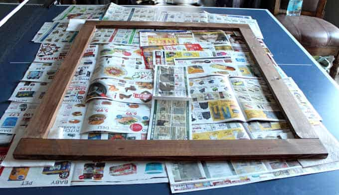 Placing stained boards on newspapers in preparation for using wood glue to make frame.