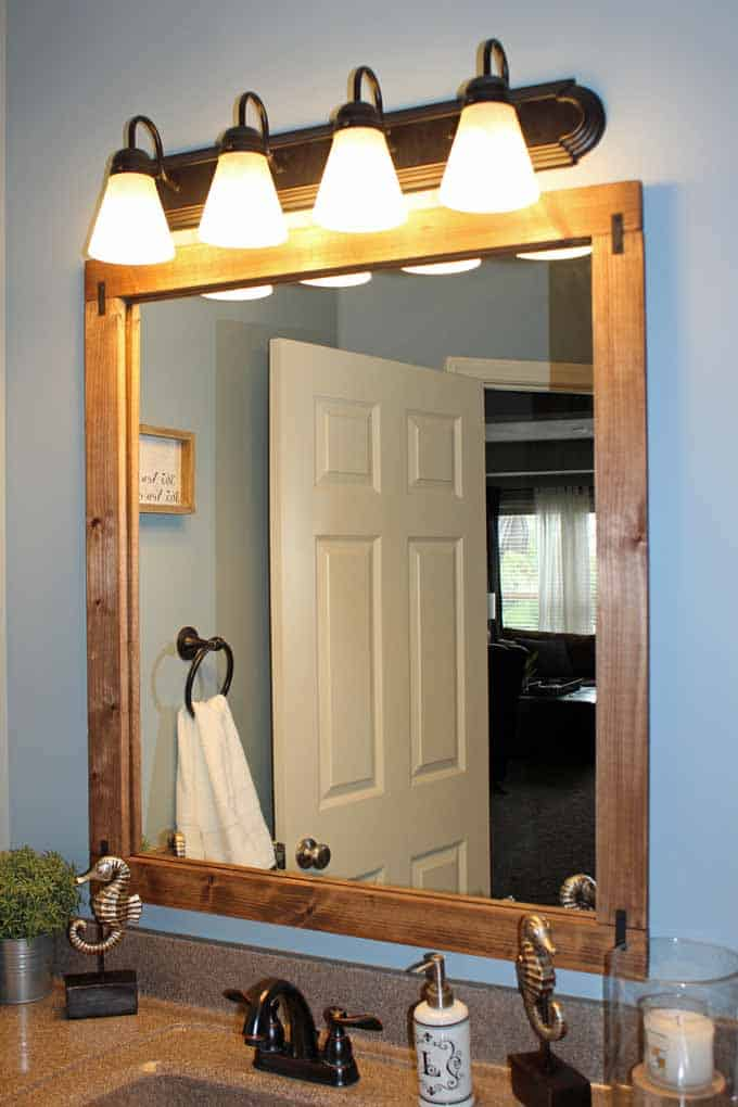 Framed bathroom mirror with lights above