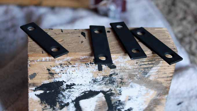 Painting hardware black using chalk paint or spray paint to match other decor.