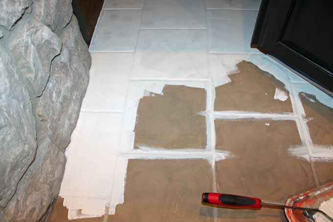 Priming outdated tile floors using INSL-X STIX primer prior to painting with stencils.
