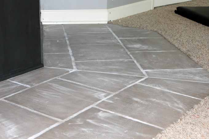 Sand the tile prior to applying primer when preparing floors for stencils / painting.