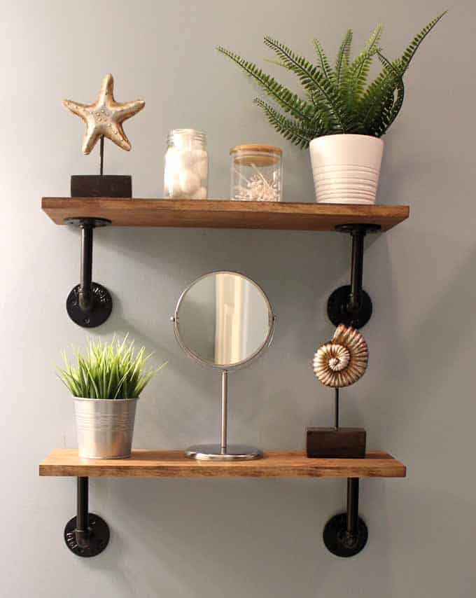 DIY farmhouse shelves in the guest bathroom above toilet and styled with IKEA faux plants and other bathroom accessories.