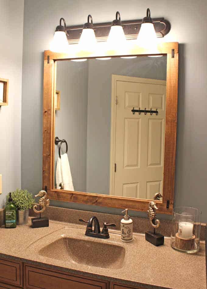 Guest bathroom with DIY wood frame around mirror above vanity.