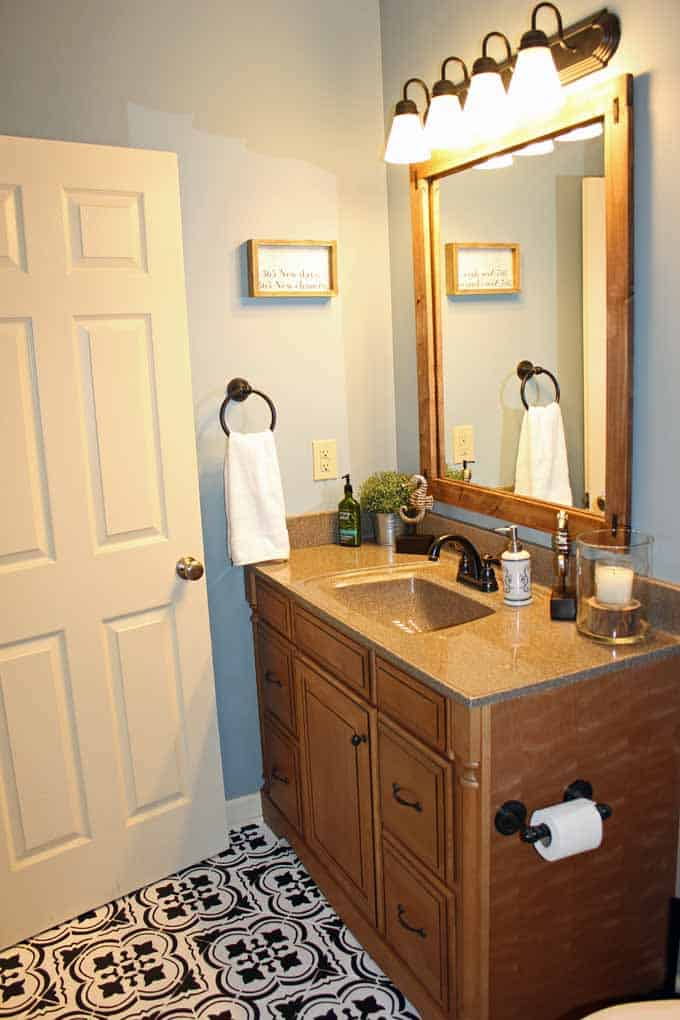 Bathroom makeover with framed mirror, painted walls in Nimbus gray, and Santa Ana stenciled tile floors.