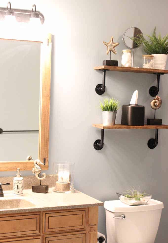 Industrial rustic shelves in a guest bathroom with DIY wood frame around builder grade mirror.