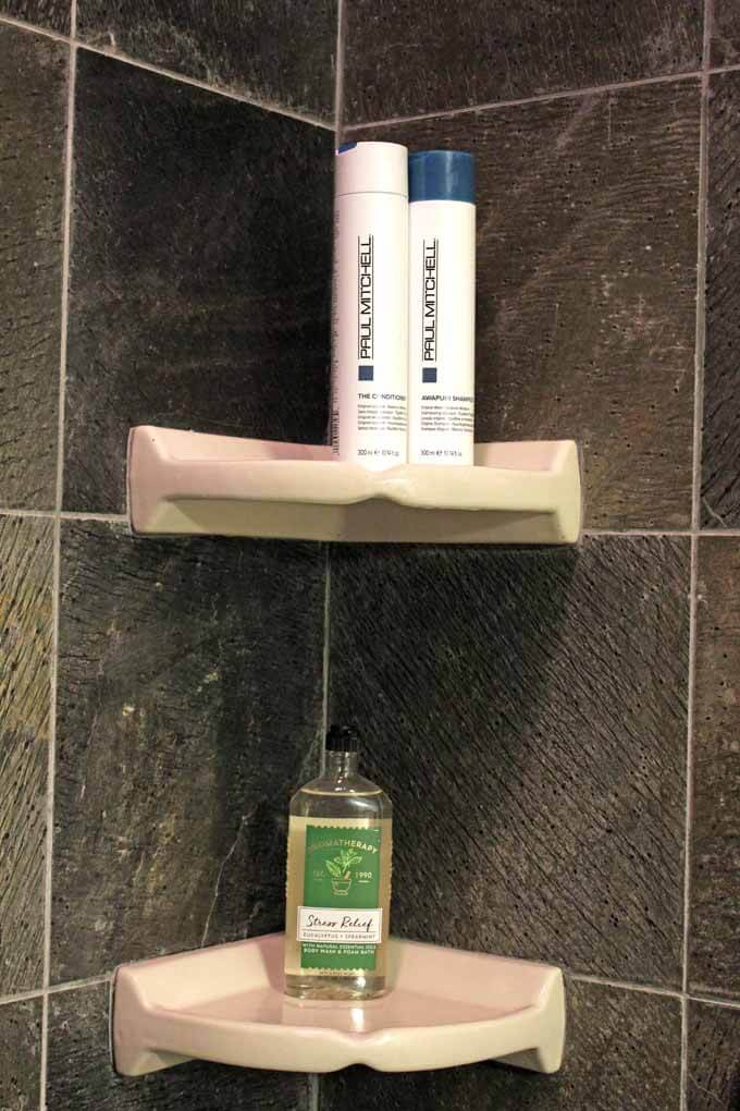 Bath and Body works Stress Relief body wash and Paul Mitchel shampoo and conditioner in shower.