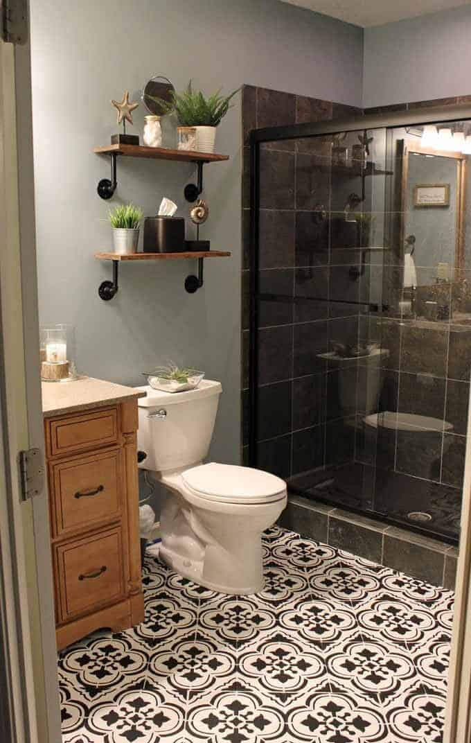 Basement bathroom with Santa Ana Stenciled floor tile, industrial wood shelves that are decorated with faux IKEA plants above toilet.