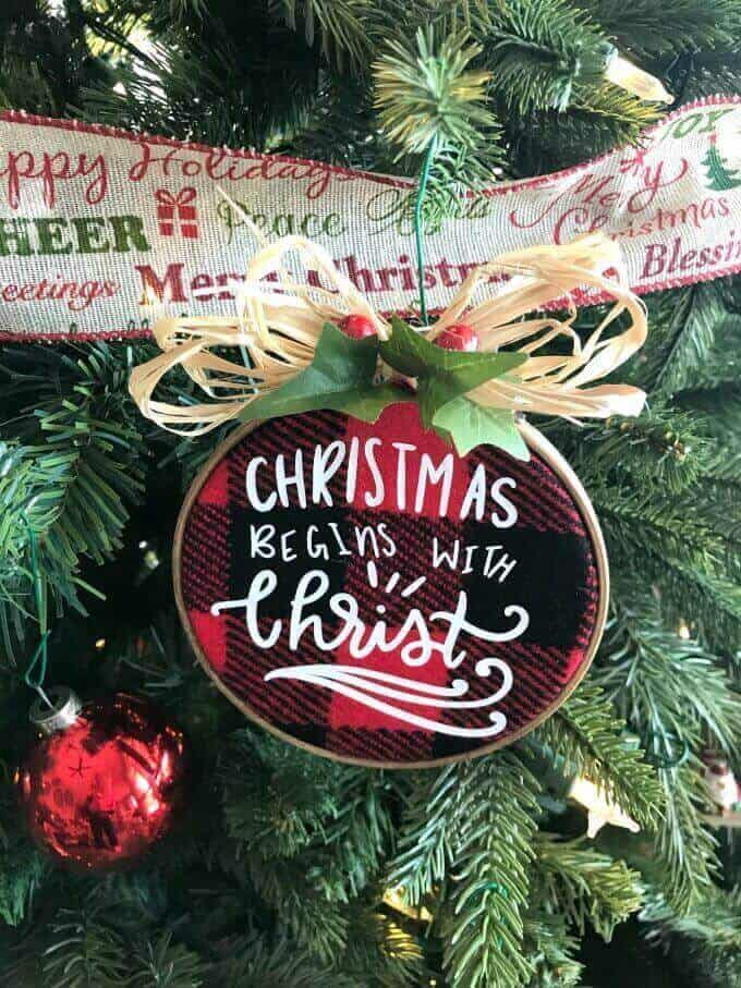 """Christmas Begins with Christ"" buffalo plaid ornament on a Christmas tree"
