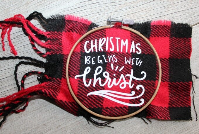 "Red and black buffalo check fabric in embroidery hoop with ""Christmas begins with Christ""."