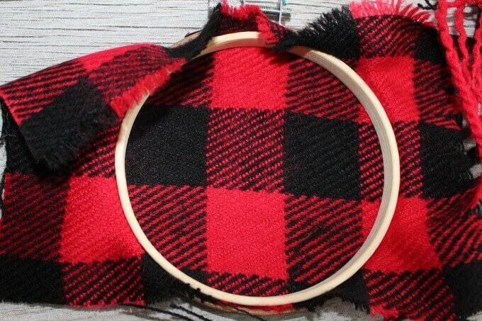 Backside of embroidery hoop ornament before cutting away excess buffalo plaid fabric
