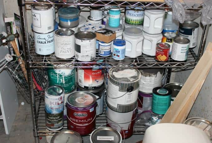 Various paint cans on metal shelving.