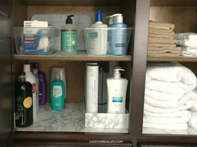 Bathroom shelving with shoe boxes covered in contact paper for prettier yet inexpensive storage.