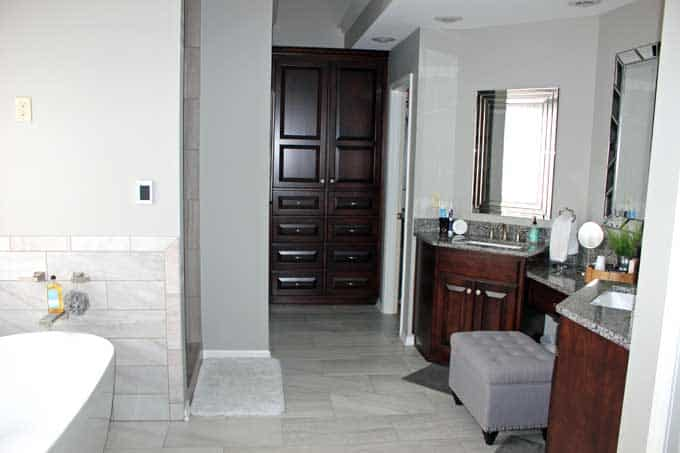 White soaker tub, gray tile, double vanities, gray painted walls.