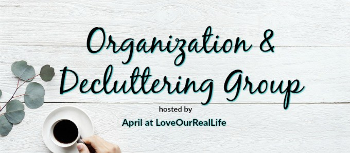 "White washed boards in background with person holding cup of coffee with words that read: ""Organization and decluttering Group hosted by April at LoveOurRealLIfe"